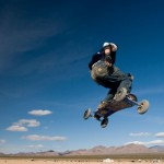 A mountainboarder in mid air with a deep blue sky