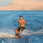 Wakeboarder in colorful shorts riding in sunset