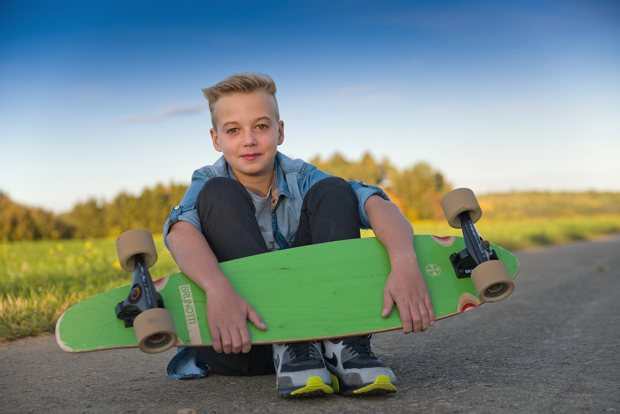child holding his longboard and ready to use it on the road