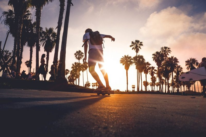 young man practicing how to longboard even on sunset